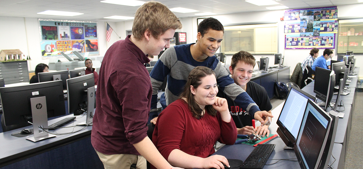 Four engineering students looking at classroom computer
