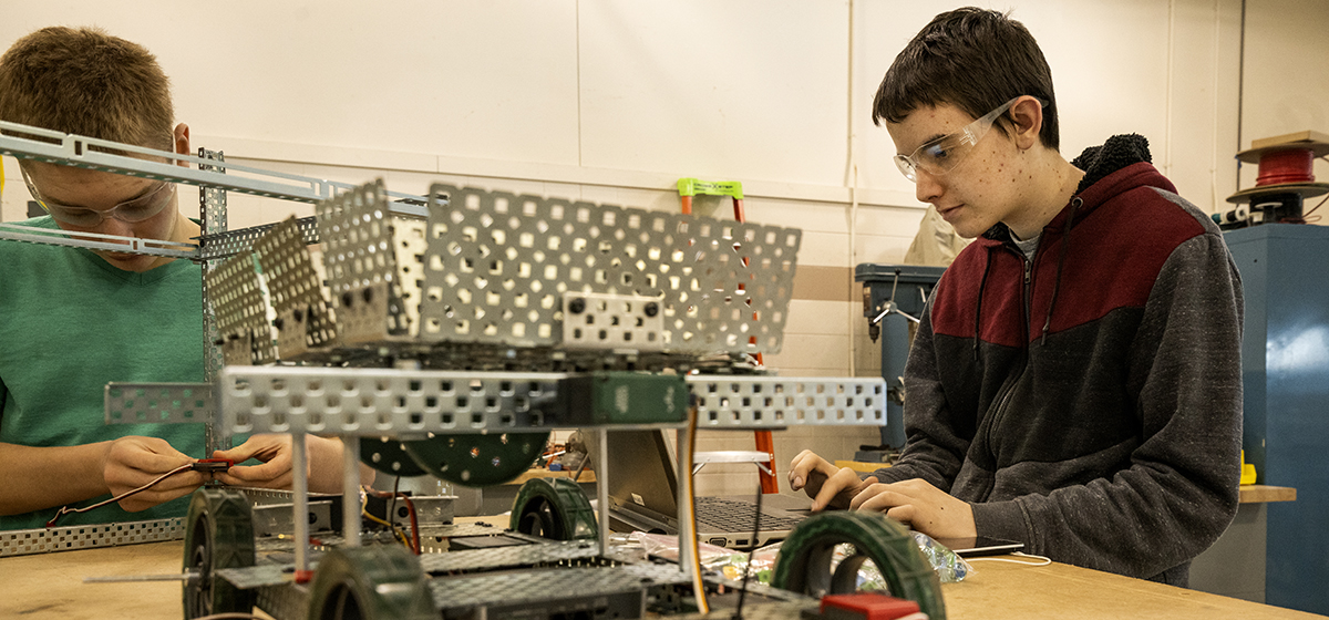 Two Engineering, Robotics, and Mechatronics students working on a robot
